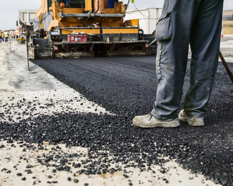 Worker,Operating,Asphalt,Paver,Machine,During,Road,Construction,And,Repairing